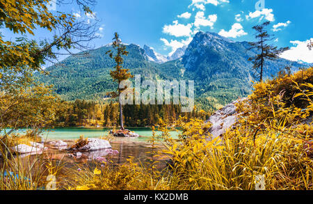 Beautiful scene of trees on a rock island in idyllic scenery at  lake Hintersee with blue sky and clouds in summer, - Stock Photo