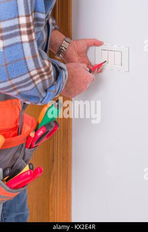 Electrician's hands assembles a standard bipolar wall socket. - Stock Photo