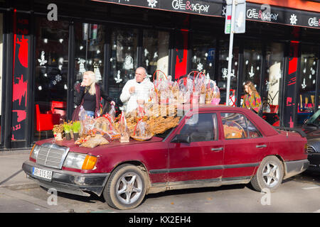 Couple of man and woman selling Serbian badnjak on placed on the hood of old Mercedes Benz car in Belgrade, Serbia - Stock Photo