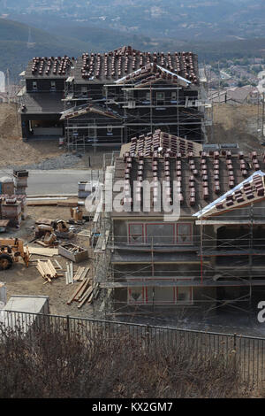 Two large new homes under construction with scaffolding, stacked roof tiles, protective covering on windows, lumber,machinery, - Stock Photo