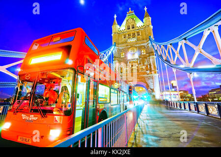 London, UK- February 4, 2017: View of Tower Bridge with tour bus passing by at night in London on February 4, 2017. - Stock Photo