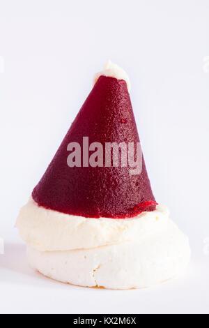 M&S mini Santa hat - crisp meringue base topped with vanilla cream and raspberry jelly isolated on white background - Stock Photo