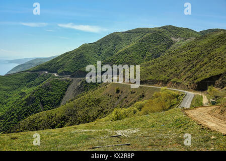 Road winding in green landscape under blue sky with white fluffy clouds - Stock Photo