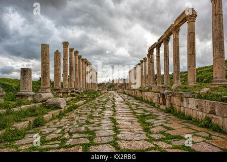 A  collonade street in the ancient city of Gerasa after a storm with dark grey clouds - Stock Photo