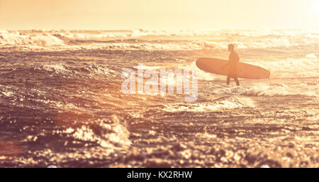 Surfers on an ocean beach. silhouette of the surfer - Stock Photo