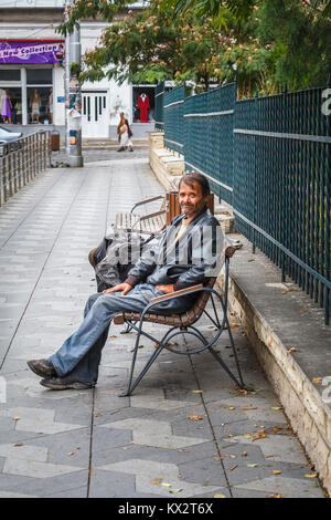 Typical down and out poor old man sitting on a roadside bench begging from passers by in Bucharest, capital city - Stock Photo