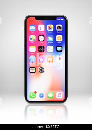 Apple iPhone X, large screen smartphone, with colorful desktop on its display. The phone is isolated on light gray - Stock Photo