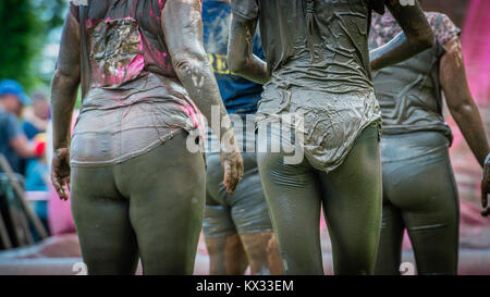 4 friends stand covered in mud after the Pretty Muddy 5k Race for Life charity fun run at Windsor Racecourse 2017 - Stock Photo