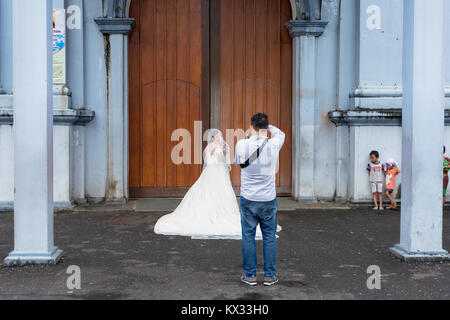 A wedding photographer taking the final photos before the bride in her white wedding dress enters the church whilst - Stock Photo
