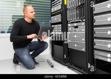 Consultant Using Laptop While Monitoring Servers In Datacenter - Stock Photo