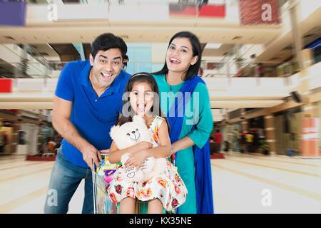 Happy Family Pushing Shopping Cart in mall having fun Cheerful - Stock Photo