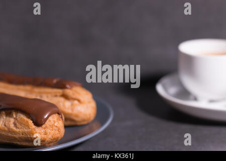 home backed eclairs with a cup of coffee - Stock Photo