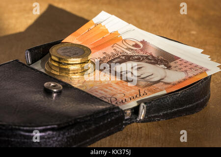 New £10 notes and £1 coins, pound / pounds sterling currency, on a leather purse. Concept of British / UK money, - Stock Photo