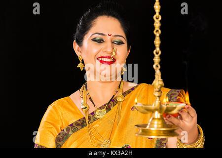 Indian Marathi Lady Deepawali Festival Burning Oil Lamps - Stock Photo