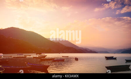 Sunset over lake filled with wooden boats in Pokhara Nepal - Stock Photo