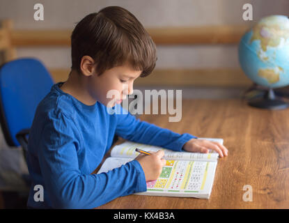 Little boy solving mathematics examples in exercise book, homework - Stock Photo