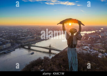 Budapest, Hungary - Aerial panoramic sunrise view at the Statue of Liberty with Liberty Bridge and sightseeing boat - Stock Photo