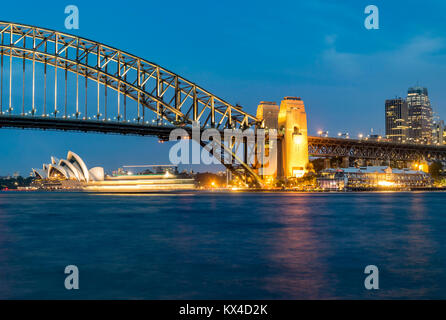 Night panorama of Sydney Harbour, Australia. Cityscape at night, Sydney Harbour Bridge, ferry passes in front of - Stock Photo