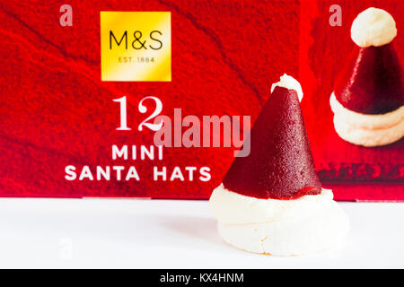 M&S mini Santa hats - crisp meringue base topped with vanilla cream and raspberry jelly - one removed and set in - Stock Photo