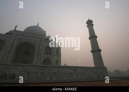 Taj mahal just after sunrise. It can barely be seen due to the high air polution in the Agra area. - Stock Photo