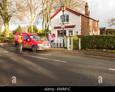 Postman collecting the mail  in his van from the post office and village shop in Cheshire village of Dunham Massey - Stock Photo