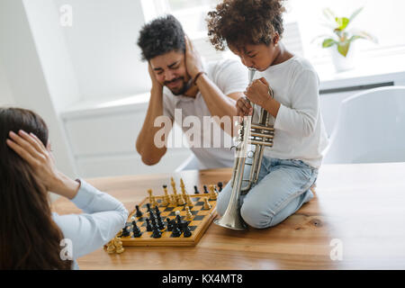 Mother and father trying to play chess while their child plays trumpet - Stock Photo