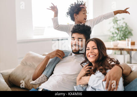 Family lifestyle portrait of a mum and dad with their kid - Stock Photo