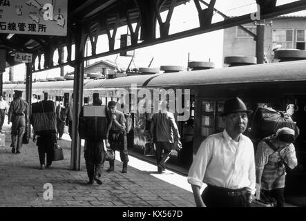 Railway station platform in Japan, 1966. Note the heavily-laden porters. - Stock Photo