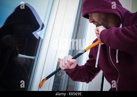 Hooded burglar forcing window to rob in the house - Stock Photo