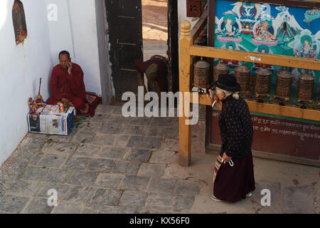 Old tibetan woman spinning prayer wheels, Boudhanath, Kathmandu, Nepal - Stock Photo