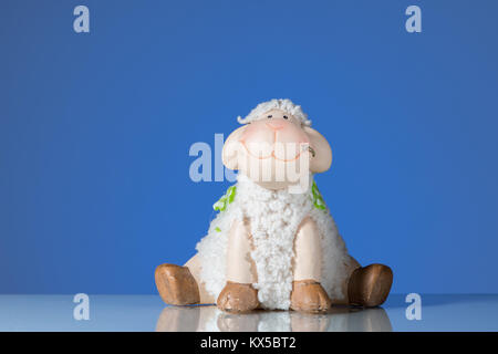 Figurine of a small funny sitting sheep blue background - Stock Photo