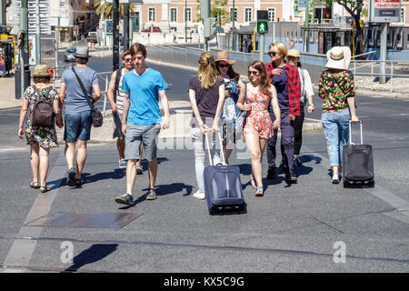 Lisbon Portugal Largo do Rato street pedestrians crossing man woman young adult rolling luggage Portuguese Europe - Stock Photo