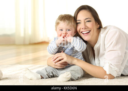 Smiley mother and her baby looking at you lying on the floor at home - Stock Photo
