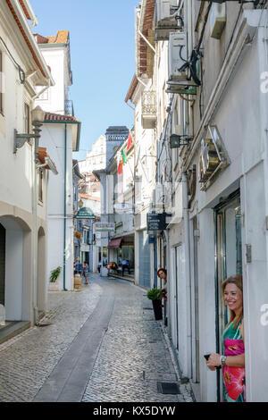 Coimbra Portugal historic center Rua Adelino Veiga storefront business woman narrow street Portuguese Europe EU - Stock Photo