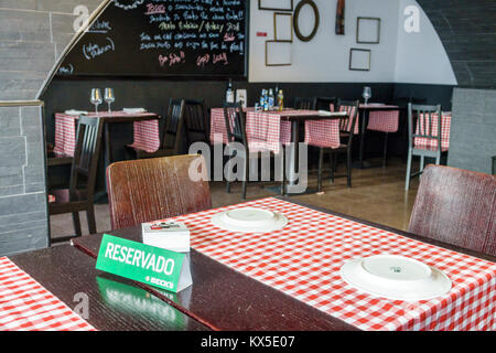 Coimbra Portugal historic center neighborhood restaurant empty red checkered tablecloth sign reserved seat Portuguese - Stock Photo