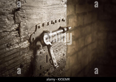 Close up view of an iron latch on an old door in a dungeon or in a castle. Vignette effect. - Stock Photo