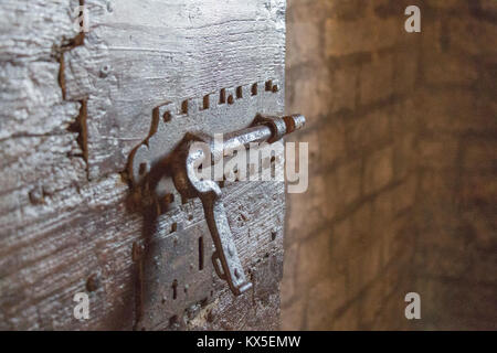 Close up view of an iron latch on an old door in a dungeon or in a castle. - Stock Photo
