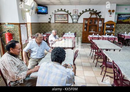 Coimbra Portugal historic center neighborhood bar restaurant man senior table sitting inside interior Portuguese - Stock Photo