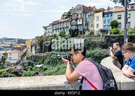 Porto Portugal Douro River historic center Luis I Bridge Metro do Porto water skyline view Asian man camera buildings - Stock Photo