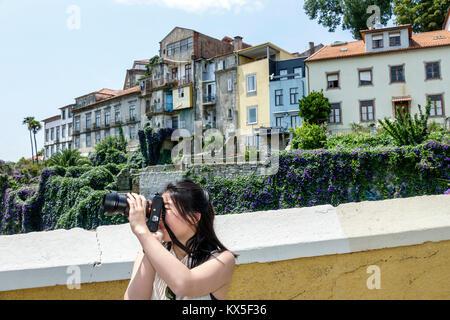 Porto Portugal Douro River Barrio La Ribeira historic center city wall Luis I Bridge skyline view Asian woman camera - Stock Photo