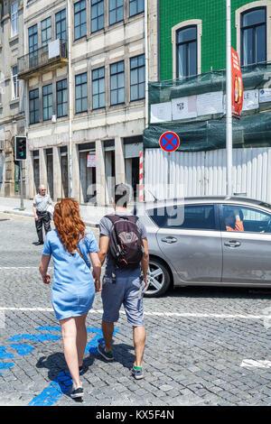 Porto Portugal historic center Calcada de Vandoma building intersection turning corner man woman Hispanic young - Stock Photo