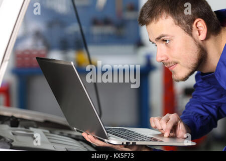 Side view portrait of a mar car mechanic checking electronic components with a laptop in a workshop - Stock Photo