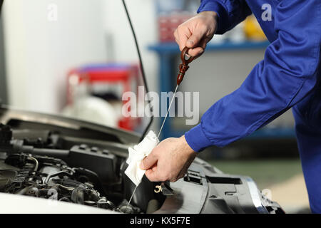Close up of a car mechanic checking oil level in a mechanical workshop - Stock Photo
