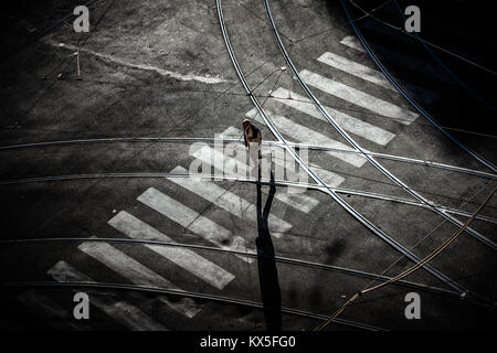 A man walks across a pedestrian crossing on a Rome street in the early morning sunshine - Stock Photo