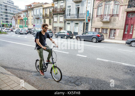 Porto Portugal Rua de Dom Manuel street Hispanic man foldable bicycle riding Portuguese Europe EU European Hispanic - Stock Photo