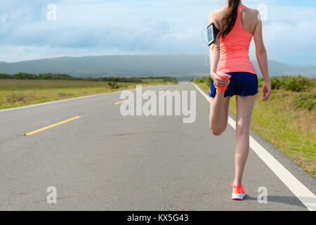 back view photo of beautiful young female runner stretching legs warm up body before running training workout on - Stock Photo