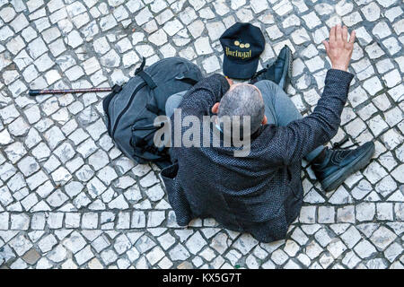 Lisbon Portugal historic center Praca dos Restauradores plaza Hispanic man senior walking cane sitting on pavement - Stock Photo