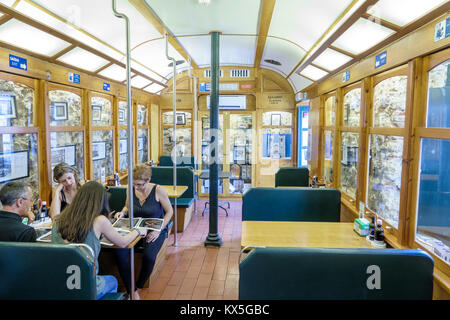 Lisbon Portugal Alfama historic neighborhood 28 Cafe restaurant tram car dining booth man woman Portuguese Europe - Stock Photo