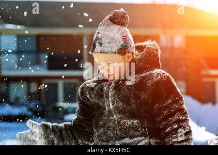 Happy little girl in white mittens walking in the winter park throws up snow Kids play outside winter season - Stock Photo