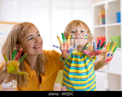Child boy and his mother with painted hands. Kid drawing and coloring with teacher in daycare center or playschool. - Stock Photo